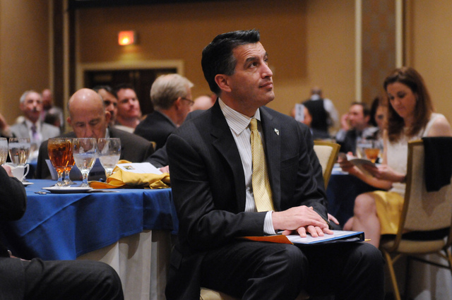 Gov. Brian Sandoval listens to a presentation during the Nevada Taxpayer Association's 92nd annual luncheon at the Orleans casino-hotel in Las Vegas Tuesday, March 4, 2014. (Erik Verduzco/Las Vega ...