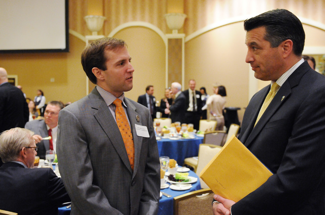 Gov. Brian Sandoval, right and Assemblyman Elliot Anderson talk to each other during the Nevada Taxpayer Association's 92nd annual luncheon at the Orleans casino-hotel in Las Vegas Tuesday, March  ...