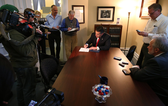 Surrounded by media, Nevada Gov. Brian Sandoval files for re-election Friday morning, March 7, 2014, at the Secretary of State's office in Carson City, Nev. (Cathleen Allison/Las Vegas Review-Journal)