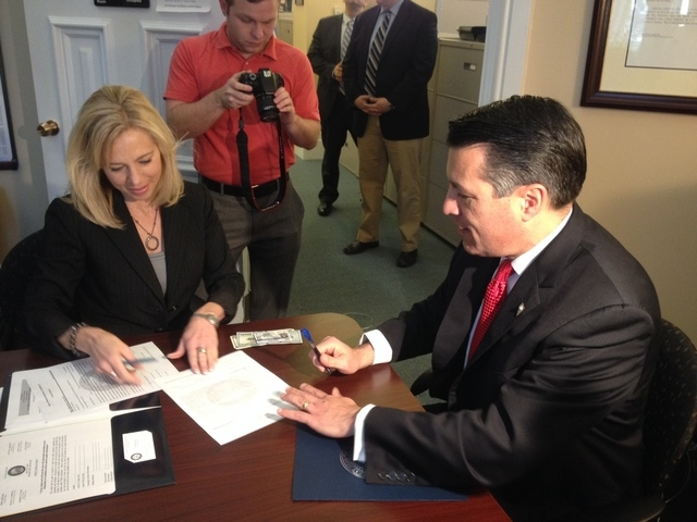 Gov. Brian Sandoval files paperwork Friday morning with Shelly Capurro, election division officer, as he files for re-election in Carson City. (Sean Whaley/Las Vegas Review-Journal Capital Bureau)