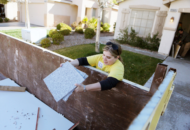 Denzila Watts throws old an countertop away outside her future Southwest home, March 1. Bank of America donated the house to Habitat for Humanity Las Vegas, and Watts joined volunteers to work on  ...
