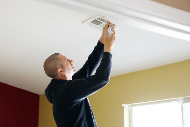 Volunteer Joe Furtado removes an air vent from Denzila Watts' future home, March 1. (Ronda Churchill/View)
