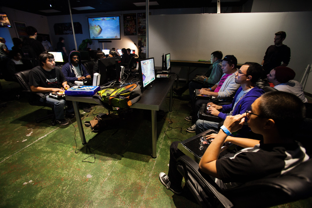 Bryan Lubay, far right, watches the action as Javier Morales, second from right, and Daniel, last name declined, next to him, compete against one another in Marvel vs. Capcom during the Bloodsport ...