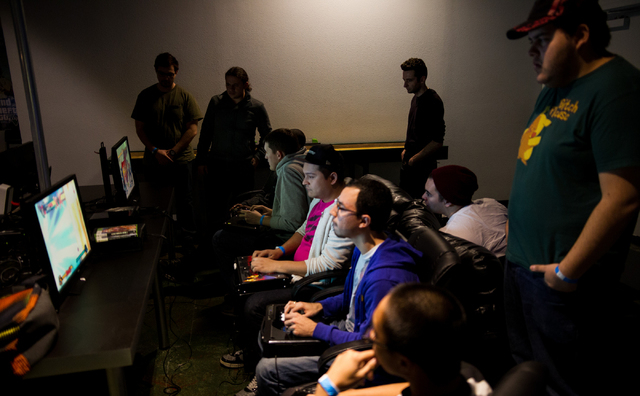 Javier Morales, center, in blue, and Daniel, last name declined, compete against one another in Marvel vs. Capcom during the Bloodsport 4 event Feb. 20 at Press Start Gaming. (Chase Stevens/View)