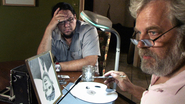 """Tim Jenison (right) demonstrates his first painting experiment to his friend, producer Penn Jillette, in a scene from the documentary """"Tim's Vermeer."""" (Carlo Villarreal/High Delft Pictures LLC)"""