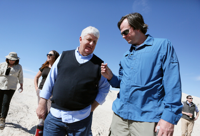 Rep. Rob Bishop, R-Utah, center, looks at a fossil with Ryann Juden (cq), right, executive government affairs liaison for the City of North Las Vegas, during a tour of a portion of the proposed Tu ...
