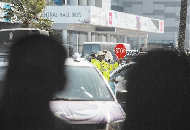 A man directs taxi traffic in front of Las Vegas Convention Center during CES on Wednesday, Jan. 8, 2014.  Uber, a rideshare and car-for-hire app thatճ popular in larger cities  isnմ a ...
