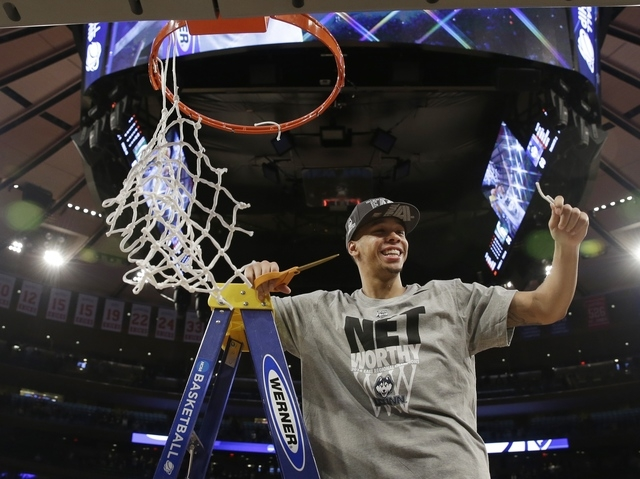 Connecticut's Shabazz Napier smiles after cutting the net after a regional final against Michigan State in the NCAA college basketball tournament on Sunday in New York. Connecticut won the game 60 ...