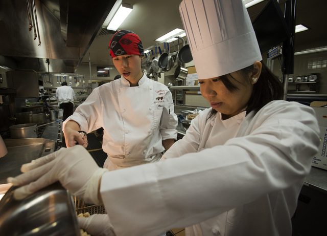 UNLV culinary students Alex Lam, left, and Kedang Pan student prepare lettuce cups with fried tofu for the UNLVino recipe tasting on Thursday. The students will prepare 25 dishes to be served at t ...