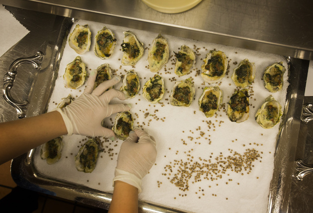 UNLV culinary student Priscilla Sulaeman places Oyster Rockerfeller during the UNLVino recipe tasting on Thursday. The students will prepare 25 dishes to be served at the 40th annual UNLVino on Ap ...
