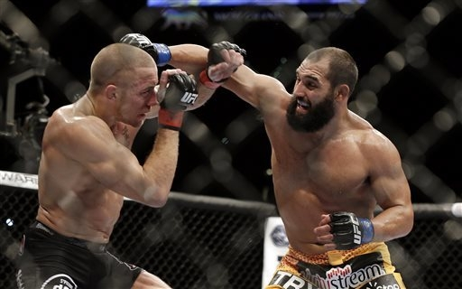 Johny Hendricks, right, exchanges punches with Georges St. Pierre, of Canada, during a UFC 167 mixed martial arts championship welterweight bout on Nov. 16, 2013, in Las Vegas. (AP Photo/Isaac Bre ...