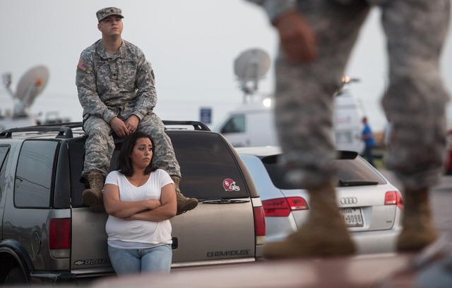Lucy Hamlin and her husband, Spc. Timothy Hamlin, wait for permission to re-enter the Fort Hood military base, where they live, after a shooting on base on Wednesday in Fort Hood, Texas. (AP Photo ...