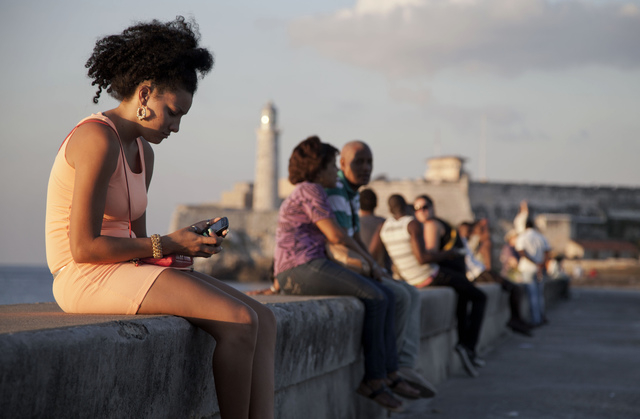 "In this March 11, 2014 photo, a woman uses her cellphone as she sits on the Malecon in Havana, Cuba. The U.S. Agency for International Development masterminded the creation of a ""Cuban Twitte ..."