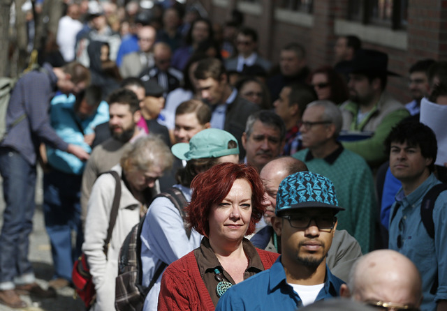 FILE - In this Thursday March 13, 2014, file photo, job seekers line up to attend a marijuana industry job far in Downtown Denver. The government issues the March jobs report on Friday, April 4, 2 ...
