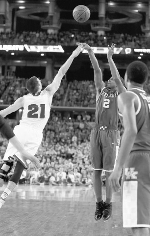 Kentucky guard Aaron Harrison (2) makes a three-point basket in the final seconds over Wisconsin guard Josh Gasser (21) to win the game 74-73 during their NCAA Final Four tournament college basket ...