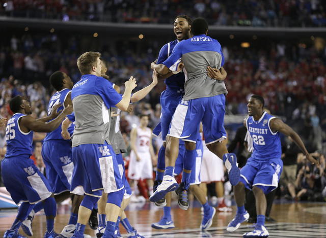 Kentucky players celebrate on the court after their 74-73 victory over Wisconsin in an NCAA Final Four tournament college basketball semifinal game Saturday, April 5, 2014, in Arlington, Texas. (A ...