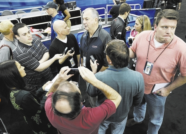 Former Connecticut head coach Jim Calhoun, center rear, is interviewed by members of the media during the team's practice for their NCAA Final Four tournament college basketball semifinal game Fri ...