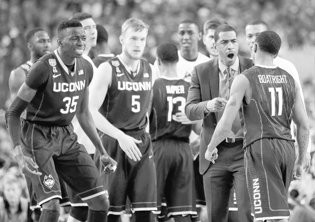 Connecticut head coach Kevin Ollie, Amida Brimah (35), Niels Giffey (5) and Ryan Boatright (11) cheer at a break against Florida during the first half of the NCAA Final Four tournament college bas ...