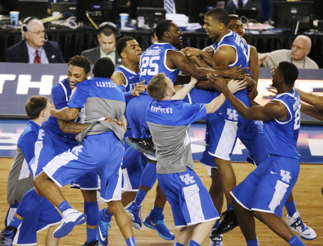 Kentucky celebrates after guard Aaron Harrison made a three-point basket in the final seconds against Wisconsin to win the game 74-73 during their NCAA Final Four tournament college basketball sem ...