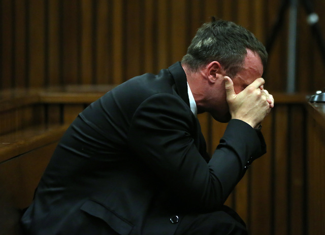 Oscar Pistorius reacts as he listens to evidence by a pathologist in court in Pretoria, South Africa, Monday, April 7, 2014. Pistorius is charged with murder  for the shooting death of his girlfri ...