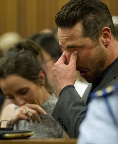 Carl Pistorius, right, listens to his brother Oscar Pistorius giving evidence in his murder trial in court in Pretoria, South Africa, Monday, April 7, 2014. Pistorius is charged with murder  for t ...