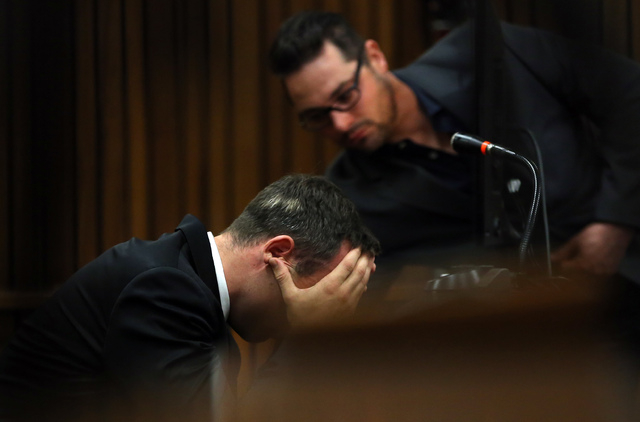 Oscar Pistorius is comforted by his brother Carl, back, as he listens to evidence by a pathologist in court in Pretoria, South Africa, Monday, April 7, 2014. Pistorius is charged with murder  for  ...