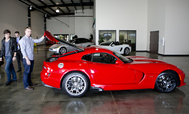 Michael Clark, 22, left,  and Douglas Sawyer, 23, right, both from Chicago rent a 2013 Dodge Viper at the Enterprise Exotic Car Collection showroom near Los Angeles International Airport on Wednes ...