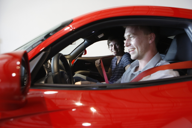 In this Wednesday, March, 26, 2014 photo, Douglas Sawyer, 23, right, and Michael Clark, 22, left, both from Chicago rent a 2013 Dodge Viper at the Enterprise Exotic Car Collection showroom near Lo ...