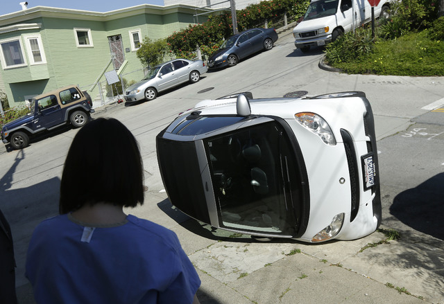 Shelley Gallivan looks toward a tipped over Smart car which belongs to her friend on the corner of Prospect and Oso streets in San Francisco, Monday, April 7, 2014. Police in San Francisco are inv ...