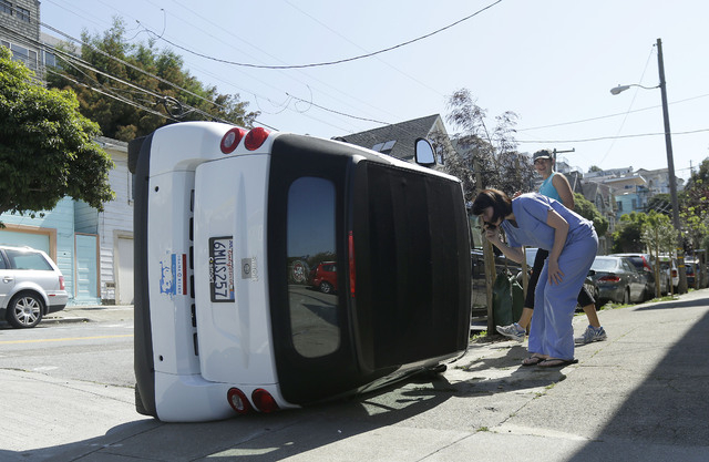 Shelley Gallivan, foreground right, looks into a tipped over Smart car which belongs to her friend on the corner of Prospect and Oso streets in San Francisco, Monday, April 7, 2014. Police in San  ...