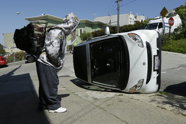 A man looks at a tipped over Smart car on the corner of Prospect and Oso streets in San Francisco, Monday, April 7, 2014. Police in San Francisco are investigating why four Smart cars were flipped ...