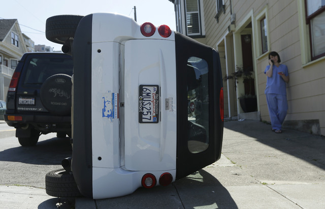 Shelley Gallivan, right, talks on the phone next to a tipped over Smart car which belongs to her friend on the corner of Prospect and Oso streets in San Francisco, Monday, April 7, 2014. Police in ...