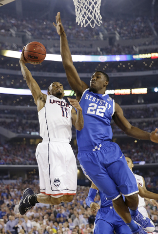 Connecticut guard Ryan Boatright, left, drives to the basket past Kentucky forward Alex Poythress during the first half of the NCAA Final Four tournament college basketball championship game Monda ...