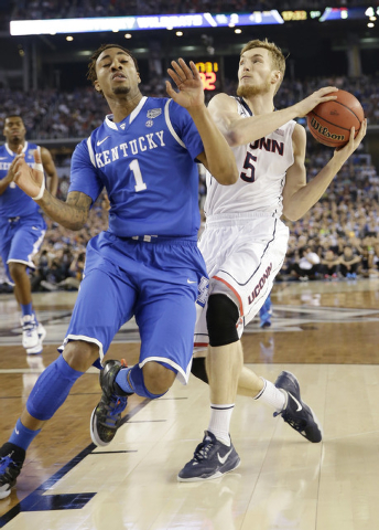 Connecticut guard Niels Giffey (5) takes the ball behind Kentucky guard James Young (1) during the first half of the NCAA Final Four tournament college basketball championship game Monday, April 7 ...