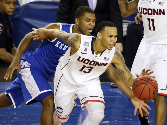Connecticut guard Shabazz Napier (13) tries to control the ball as Kentucky guard Aaron Harrison (2) defends during the second half of the NCAA Final Four tournament college basketball championshi ...