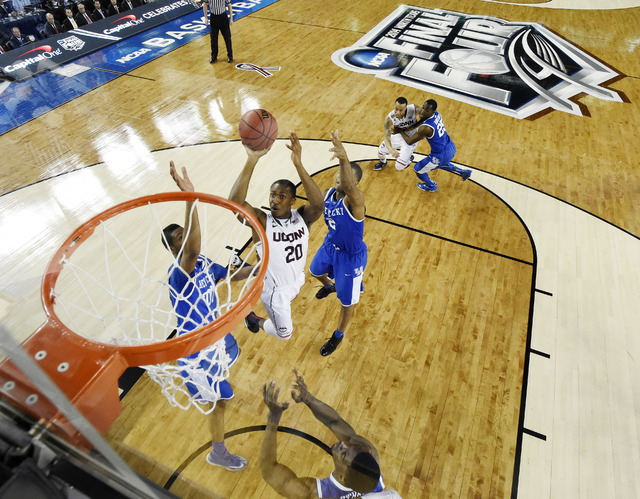 Connecticut guard Lasan Kromah (20) shoots between defenders Kentucky forward Marcus Lee (00) and guard Aaron Harrison (2) during the first half of the NCAA Final Four tournament college basketbal ...