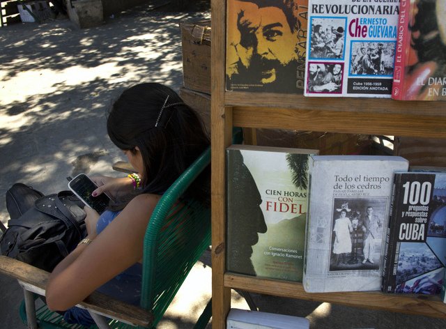 A book street vendor passes the time on her smart phone as she waits for customers in Havana, Cuba, Tuesday, April 1, 2014. The Obama administration secretly financed a social network in Cuba to s ...