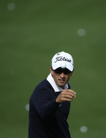Adam Scott, of Australia, catches a golf ball from his caddie on the driving range during a practice round for the Masters golf tournament Tuesday, April 8, 2014, in Augusta, Ga. (AP Photo/Matt Sl ...