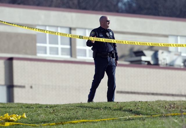 A police officer stands by the scene outside Franklin Regional High School where more then a dozen students were stabbed by a knife wielding suspect on Wednesday, April 9, 2014, in Murrysville, Pa ...