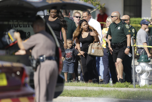 Parents with their children are escorted away with Orange County deputies after a vehicle crashed into a day care center, Wednesday, April 9, 2014, in Winter Park, Fla. At least 15 people were inj ...