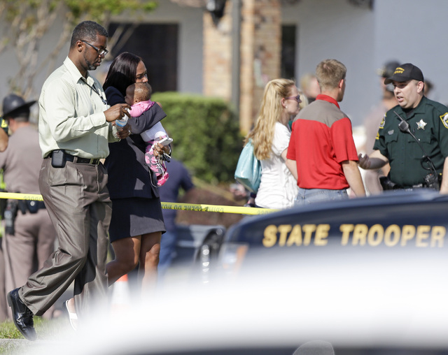 Parents leave a daycare center with their children after a vehicle crashed into the center, Wednesday, April 9, 2014, in Winter Park, Fla. At least 15 people were injured, including children. (AP  ...