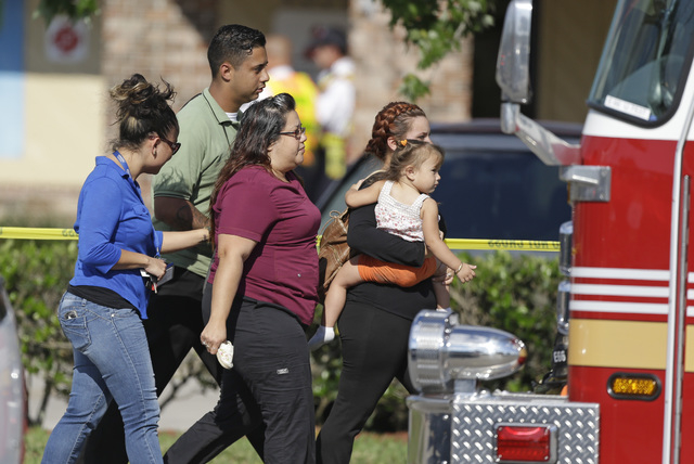 Parents and relatives leave a day care center with their children after a vehicle crashed into the center, Wednesday, April 9, 2014, in Winter Park, Fla. At least 15 people were injured, including ...