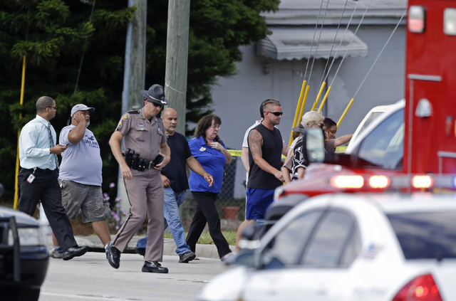A Florida state trooper, center, escorts a group of parents to a day care center to pick up their children after a vehicle crashed into the center, Wednesday, April 9, 2014, in Winter Park, Fla. A ...