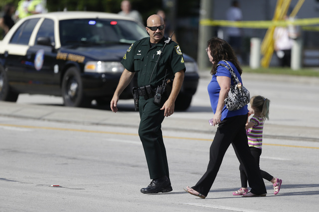 An Orange County Sheriff's deputy, left, escorts a mother and her child across a street after a vehicle crashed into a day care center, Wednesday, April 9, 2014, in Winter Park, Fla. At least 15 p ...