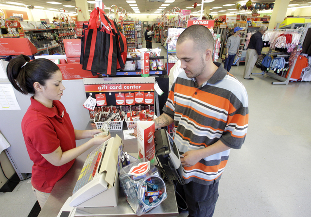 FILE - In this file photo taken Dec. 14, 2010, Family Dollar employee Pamela Ramos, left, assists John Conner with a purchase at a store in Waco, Texas. Family Dollar on Thursday, April 10, 2014 s ...