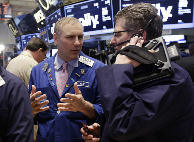 Specialist Geoffrey Friedman, left, and trader Sean Spain work on the floor of the New York Stock Exchange Thursday, April 10, 2014.  U.S. stock indexes are slipping lower in early trading Thursda ...