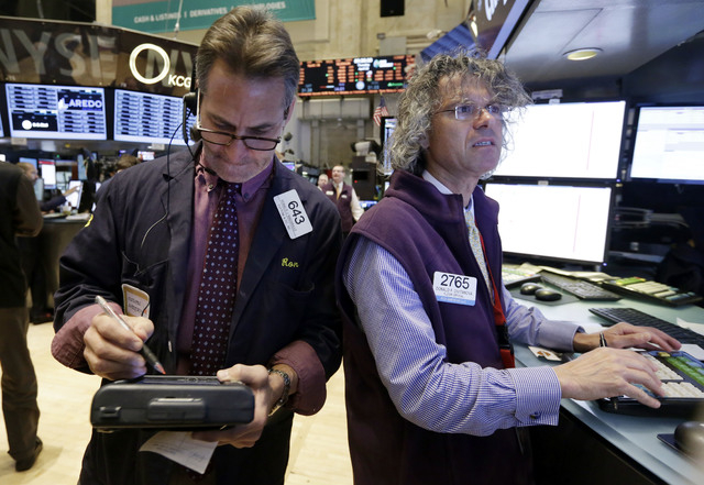 Trader Ronald Madarasz, left, and specialist Donald Civitanova work on the floor of the New York Stock Exchange Thursday, April 10, 2014.  U.S. stock indexes are slipping lower in early trading Th ...