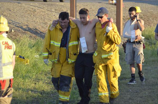 Rescuers tend to walking wounded after a fiery crash involving several vehicles, Thursday, April 10, 2014, just north of Orland, Calif., that left at least nine dead. Authorities said it is not ye ...