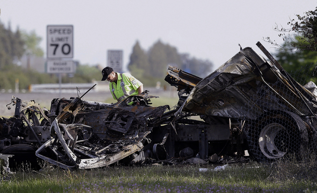 A worker looks over the demolished cab of FedEx truck on Friday that crashed into a tour bus on Interstate 5 Thursday in Orland, Calif. Ten people were killed and dozens injured in the fiery crash ...