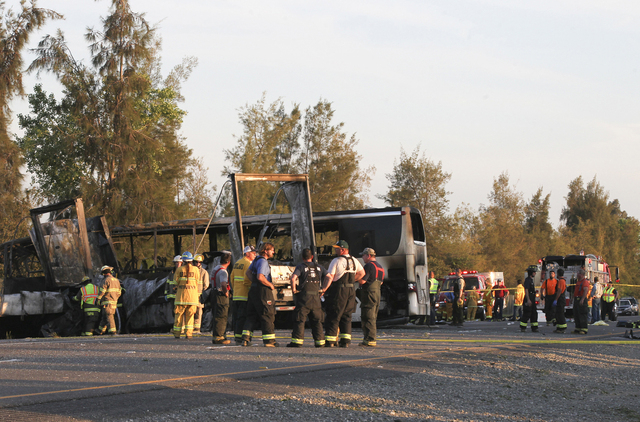 Rescue workers, police and firefighters work the scene where 10 people were killed in a three-vehicle crash involving a bus carrying high school students on a visit to a college, Thursday near Orl ...